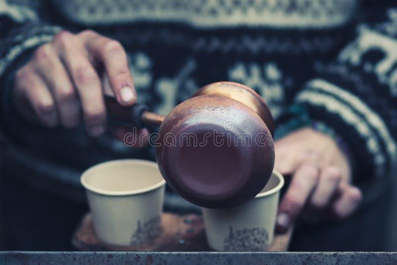 烹调和倾吐在纸杯的街道咖啡 有选择聚焦的特写镜头手在咖啡罐 免版税库存照片