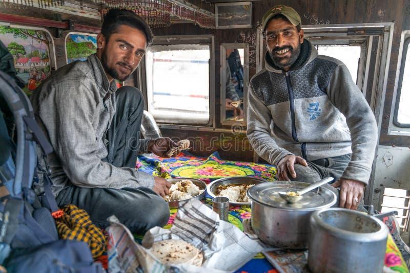 烹调和吃与印度司机的看法在卡车里面 免版税库存照片