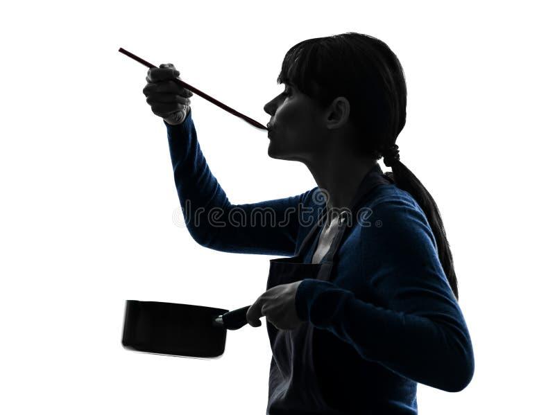 烹调品尝平底深锅剪影的妇女 免版税库存图片