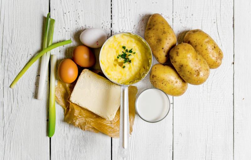 烹调土豆泥成份:土豆、牛奶、鸡蛋,黄油和其他在一张白色木桌上 免版税库存照片