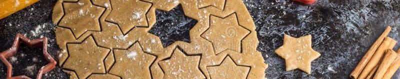烹调圣诞节与成份的姜饼曲奇饼横幅在黑暗的背景 图库摄影