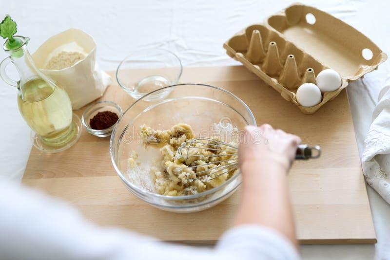 烹调圣诞节巧克力碎片松饼 果仁巧克力的,杯形蛋糕,薄煎饼混合的成份 妇女手准备 免版税库存图片