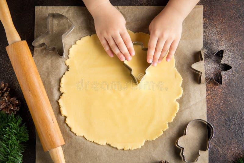 烹调圣诞节曲奇饼的孩子,切了与曲奇饼切削刀,家庭传统,可口甜假日食物的面团 免版税库存图片