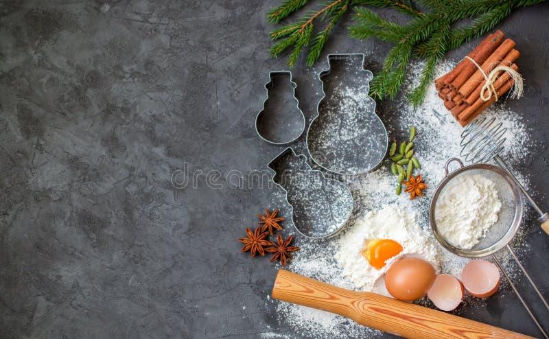 烹调圣诞节烘烤 面团和香料的成份在桌上 面粉,鸡蛋,肉桂条,豆蔻果实,星美洲黑杜鹃 免版税库存图片