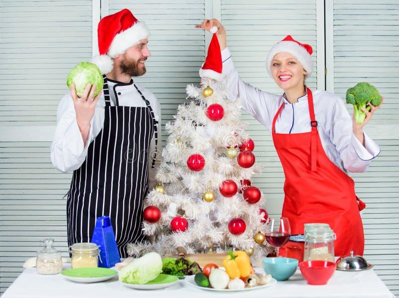 烹调圣诞节膳食 男人和妇女厨师在圣诞树附近的圣诞老人帽子 秘方是爱 圣诞节食谱 库存照片