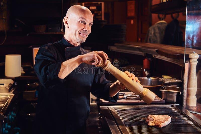 烹调在一个厨房的大厨可口牛排在餐馆,以子弹密击与胡椒磨的肉 免版税库存图片