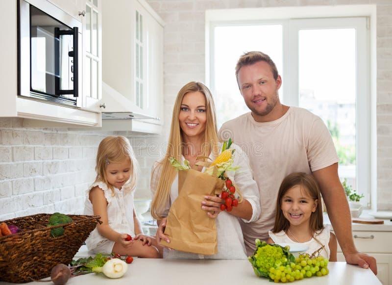 烹调在一个现代厨房设置的家庭 免版税图库摄影
