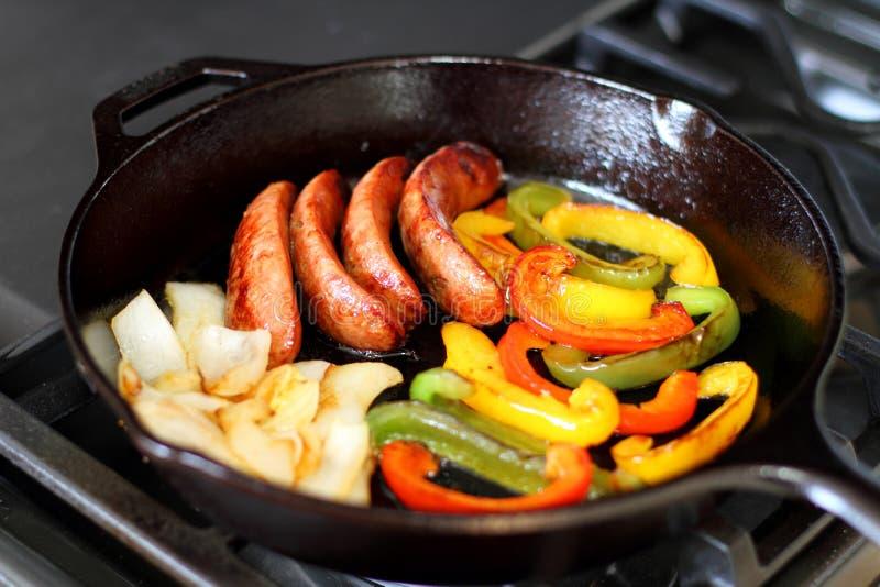 烹调在一个生铁长柄浅锅的火炉的香肠 图库摄影