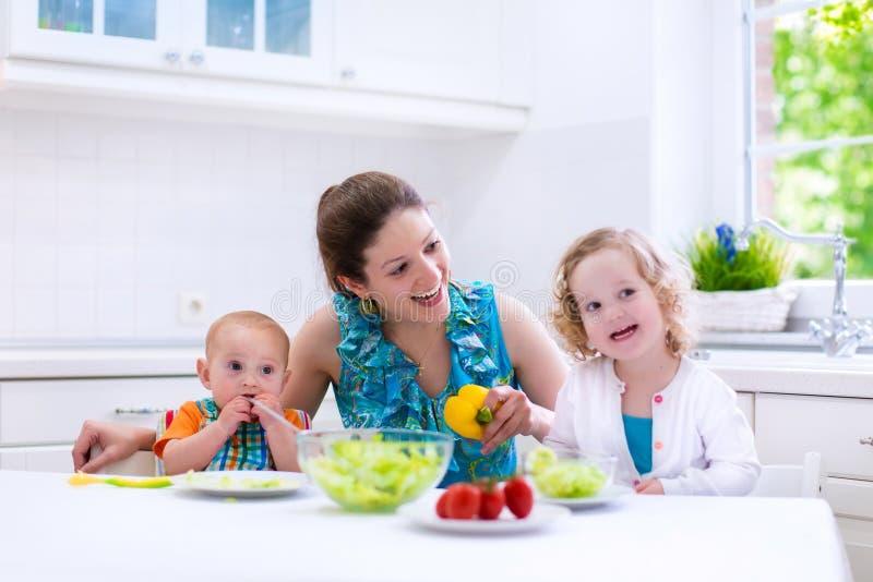 烹调在一个白色厨房里的母亲和孩子 免版税库存照片