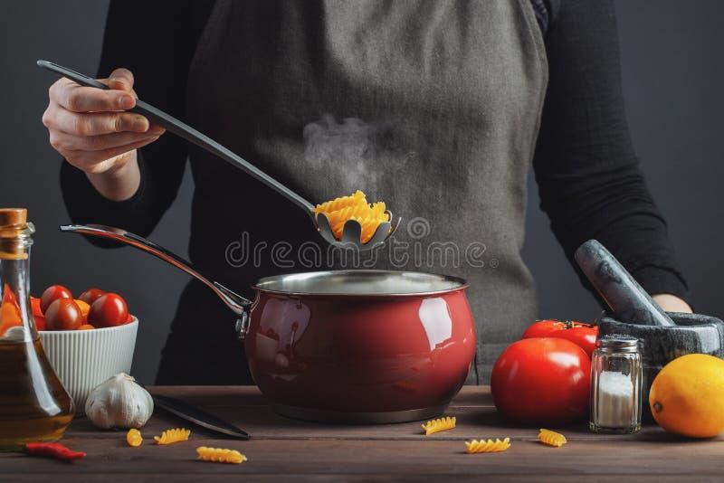 烹调在一个罐的意大利面团在厨房里,准备食物,膳食的厨师 妇女厨师拉出平底锅现成的面团fusilli 库存图片