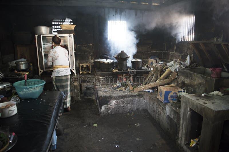 烹调在传统厨房里的巴厘语妇女 免版税图库摄影