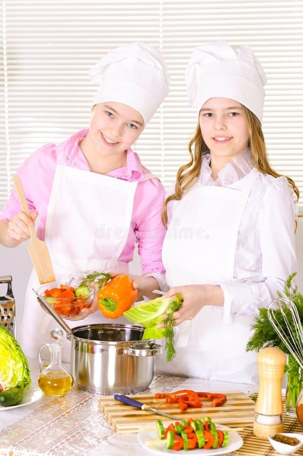 烹调在厨房的两个逗人喜爱的女孩画象  库存图片