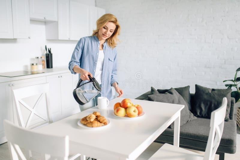 烹调在厨房的愉快的妇女早餐 图库摄影