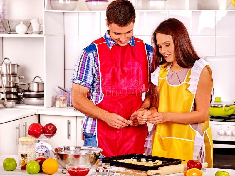 烹调在厨房的年轻家庭 免版税库存图片