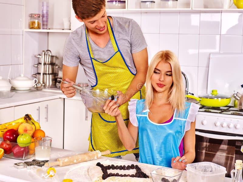 烹调在厨房的年轻家庭 库存图片