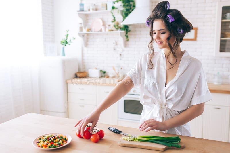 烹调在厨房里的可爱的好年轻女人 在书桌和作为裁减红辣椒的立场 大葱在书桌上被切 免版税图库摄影