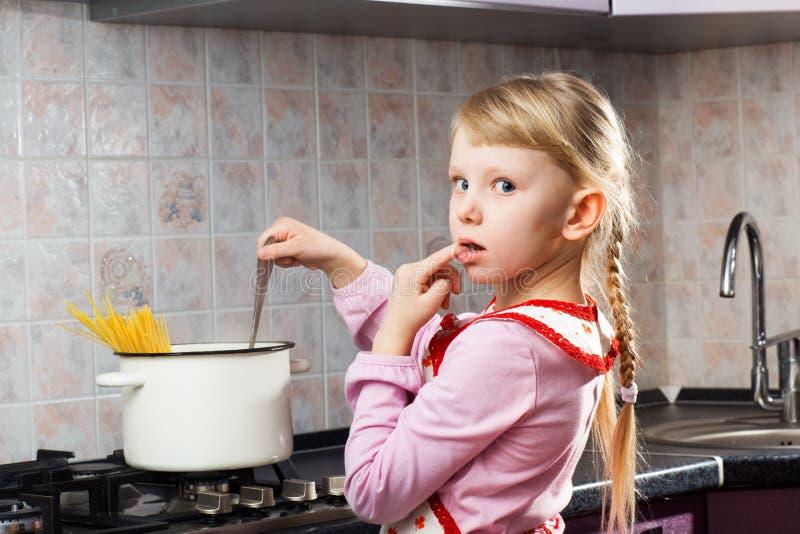 烹调在厨房里的困惑的女孩 库存照片