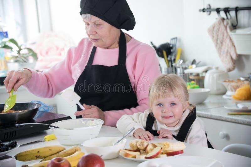 烹调在厨房里的女孩和她的祖母 库存照片