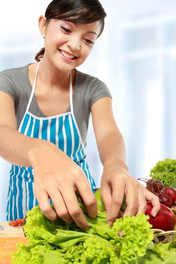 烹调在厨房里的妇女 免版税库存图片
