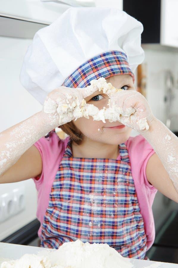 烹调在厨房里的小女孩 库存图片