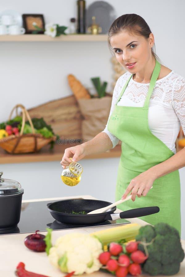 烹调在厨房里的少妇主妇 新和健康膳食的概念在家 免版税图库摄影
