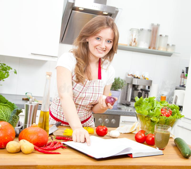 烹调在厨房里的少妇 健康食品-菜婆罗双树 库存照片