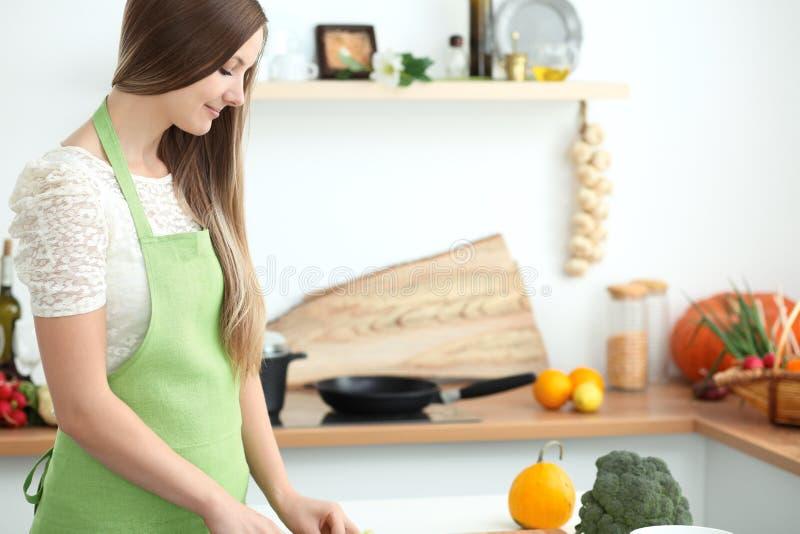 烹调在厨房里的少妇 切新鲜的沙拉的主妇 库存图片