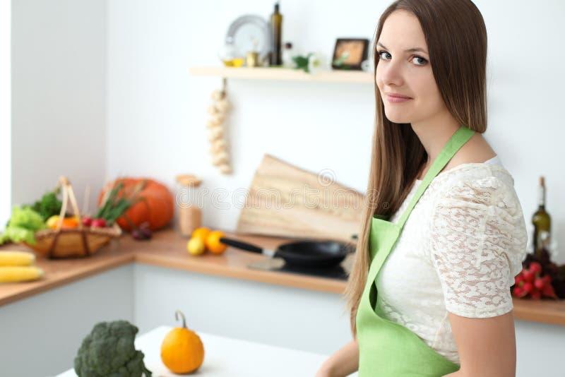 烹调在厨房里的少妇 切新鲜的沙拉的主妇 库存照片