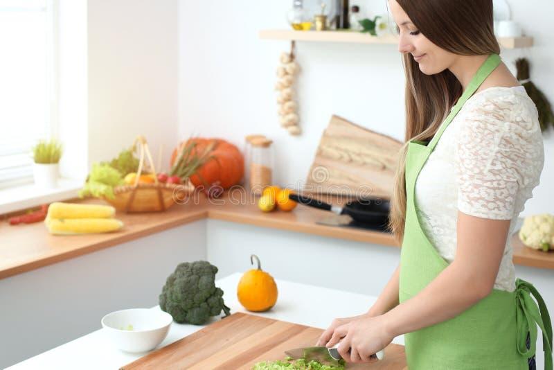烹调在厨房里的少妇 切新鲜的沙拉的主妇 图库摄影