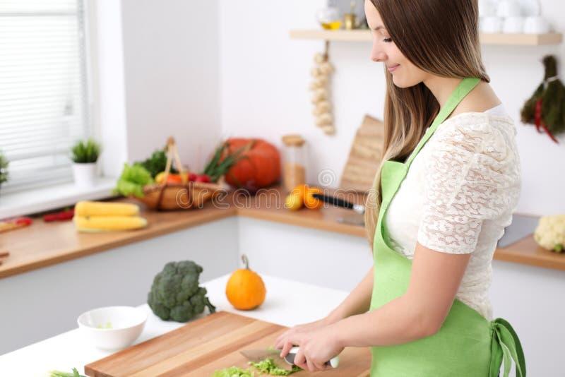 烹调在厨房里的少妇 切新鲜的沙拉的主妇 免版税图库摄影