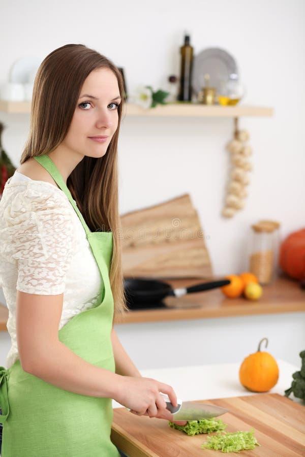 烹调在厨房里的少妇 切新鲜的沙拉的主妇 免版税库存图片