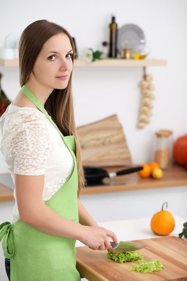 烹调在厨房里的少妇 切新鲜的沙拉的主妇 免版税库存照片
