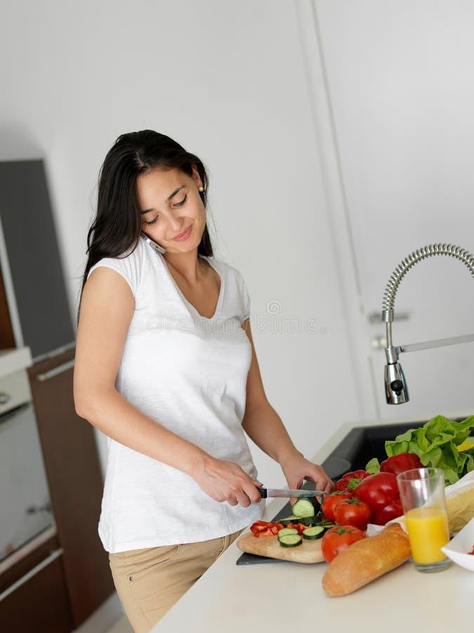 烹调在厨房里的少妇 免版税库存图片