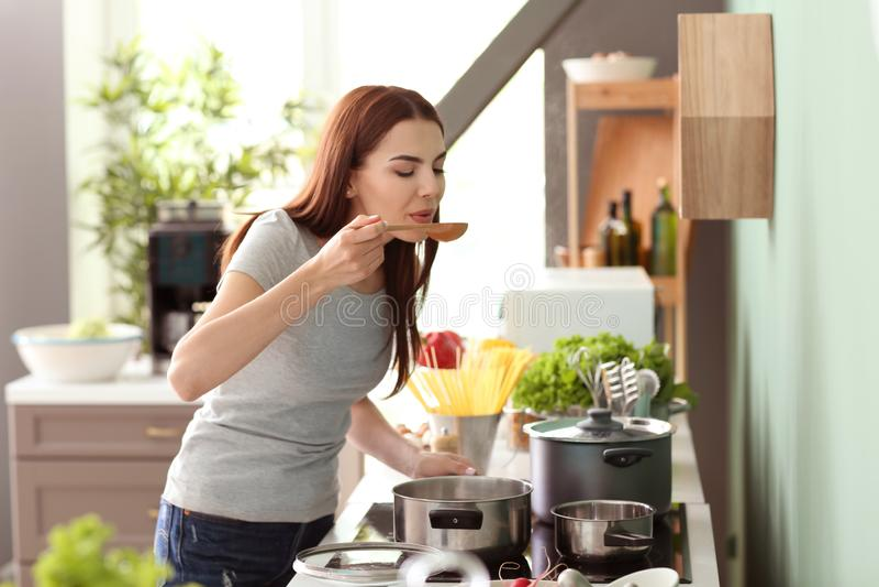 烹调在厨房里的年轻女人 库存图片