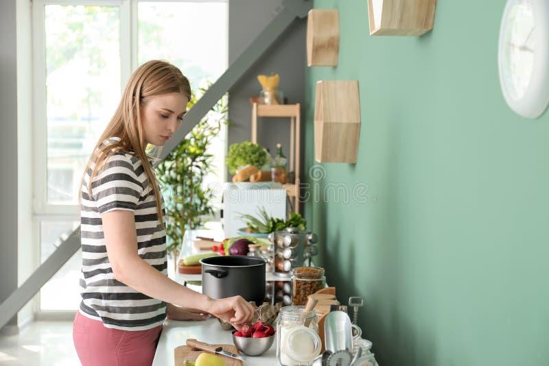 烹调在厨房里的年轻女人 库存照片