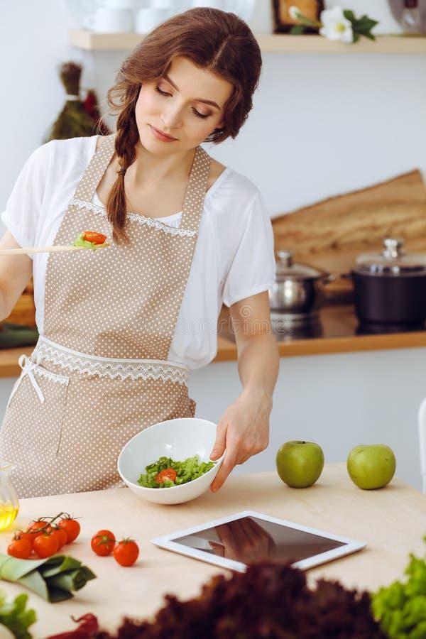 烹调在厨房里的年轻深色的妇女 主妇在她的手上的拿着木匙子 o 库存照片