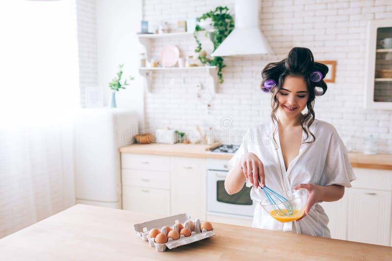 烹调在厨房里的年轻美丽的女性管家 在玻璃碗的混和的鸡蛋 看得下来和微笑 在头发的卷发的人 免版税库存照片