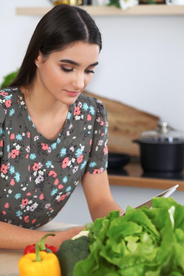 烹调在厨房里的年轻西班牙妇女或学生 使用片剂的女孩做网上购物或发现一份新的食谱 库存照片