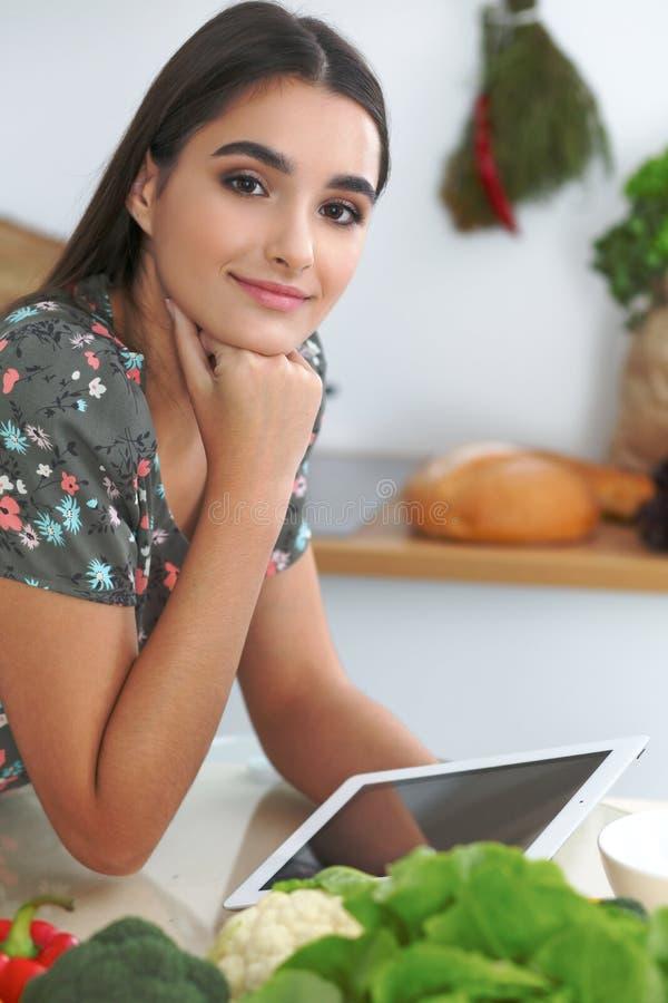 烹调在厨房里的年轻西班牙妇女或学生 使用片剂的女孩做网上购物或发现一份新的食谱 库存图片