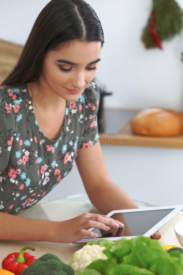 烹调在厨房里的年轻西班牙妇女或学生 使用片剂的女孩做网上购物或发现一份新的食谱 图库摄影