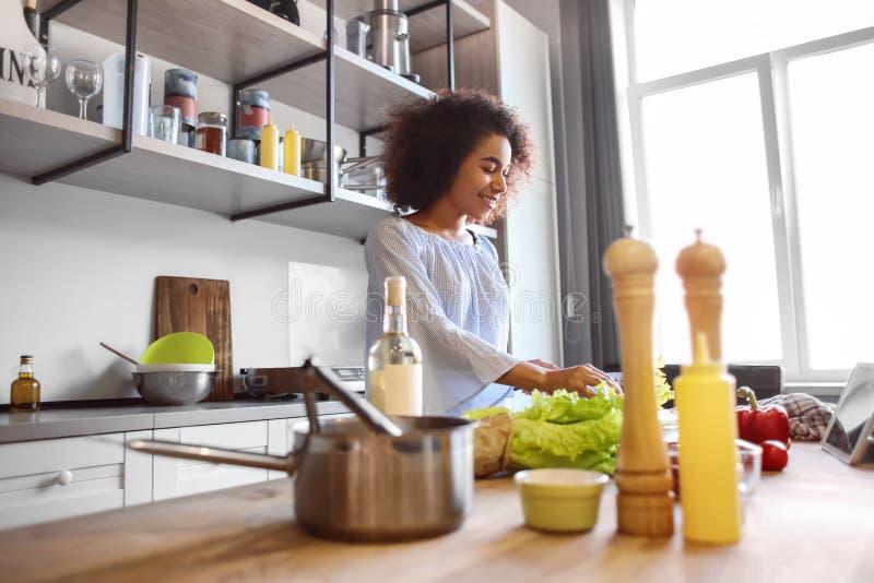 烹调在厨房里的年轻非裔美国人的妇女 免版税库存照片
