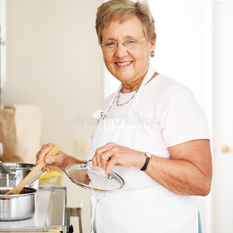 烹调在厨房里的愉快的祖母 图库摄影