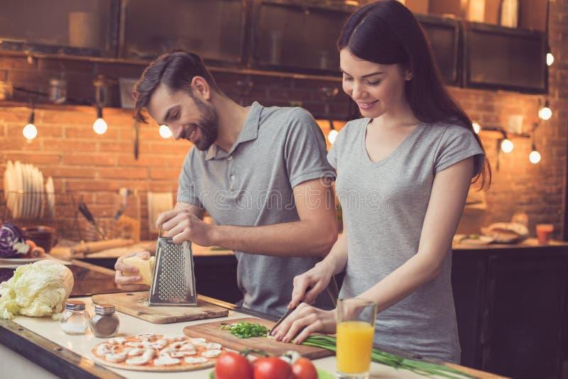 烹调在厨房里的新夫妇 免版税库存照片