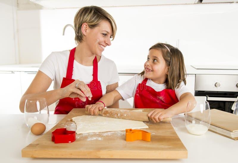 年轻烹调在厨房里的母亲和小甜女儿准备有滚针标尺的沙漠 库存照片