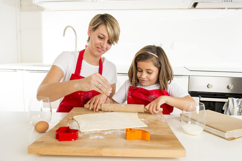 年轻烹调在厨房里的母亲和小甜女儿准备有滚针标尺的沙漠 免版税库存照片