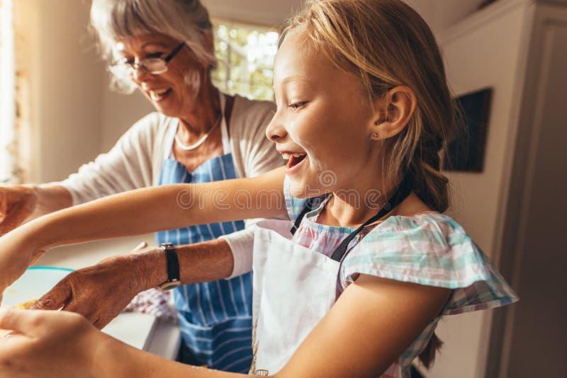烹调在厨房里的祖母和孩子 库存照片