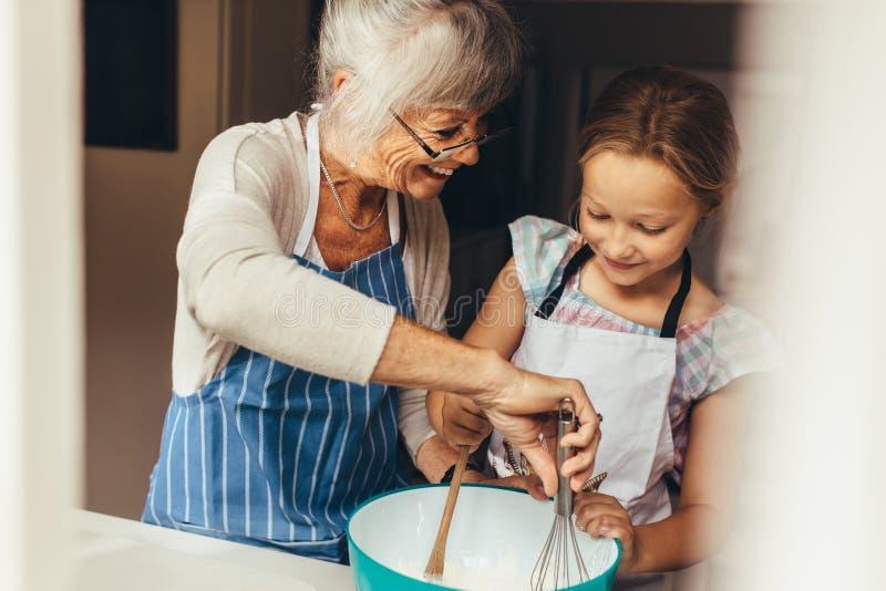 烹调在厨房里的老婆婆和孩子 免版税库存图片