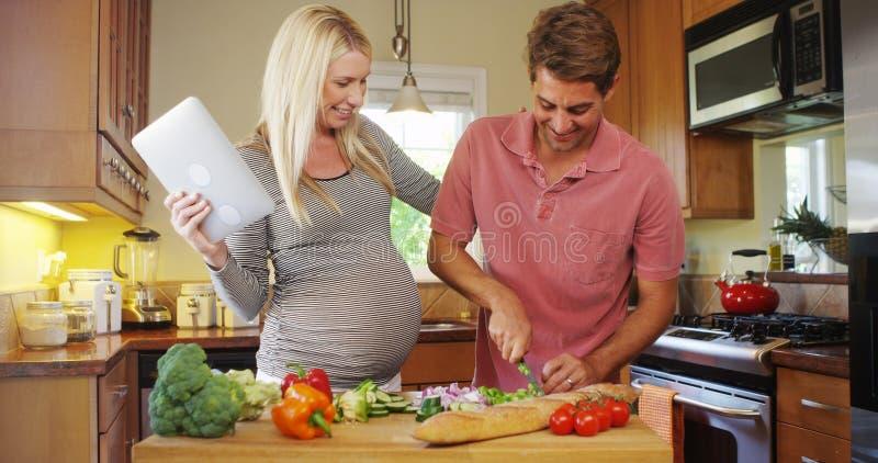 烹调在厨房里的逗人喜爱的怀孕的夫妇 免版税库存照片
