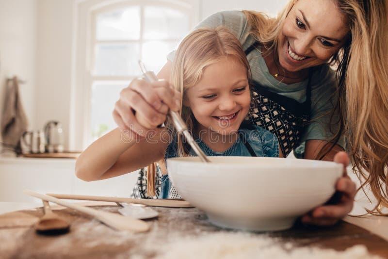 烹调在厨房里的年轻家庭 免版税库存照片