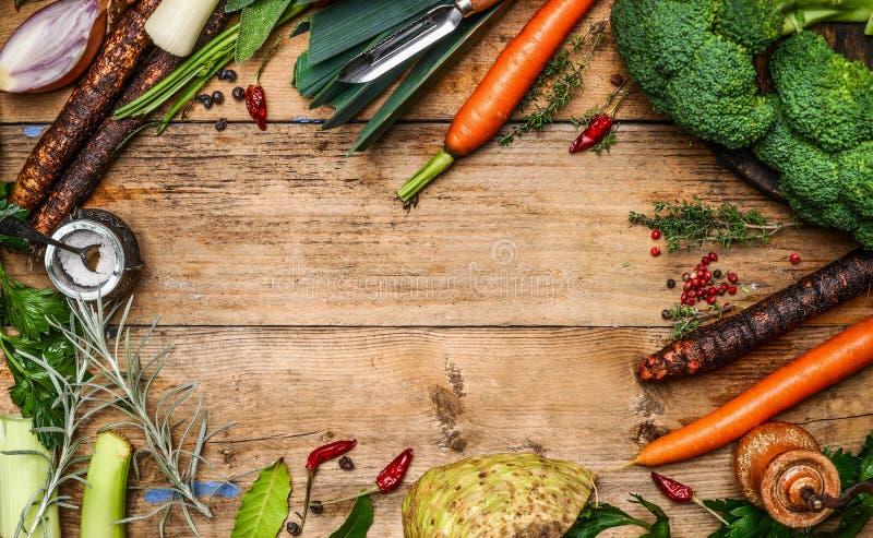 烹调在土气木背景,顶视图的汤或汤的新鲜的庭院菜成份 免版税图库摄影